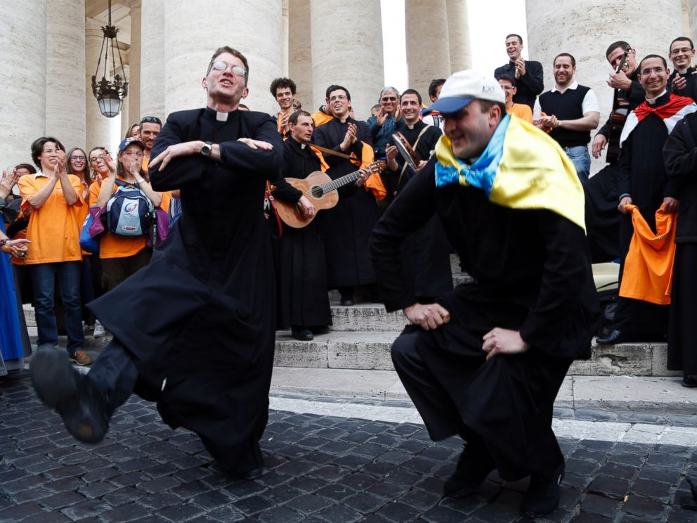 PHOTO: Two priests, one of them with an Ukrainian flag on his shoulders, dance in St. Peters Square at the Vatican, Saturday, April 26, 2014.