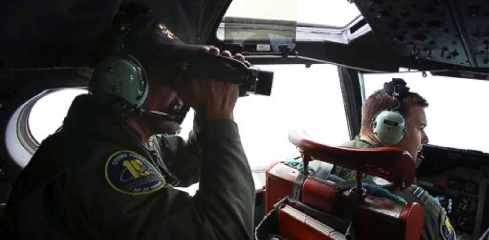 PHOTO: In this Wednesday, March 26, 2014 photo, Flight Engineer Ron Day on board a Royal Australian Air Force AP-3C Orion, searches for the missing Malaysia Airlines Flight 370 in the southern Indian Ocean.