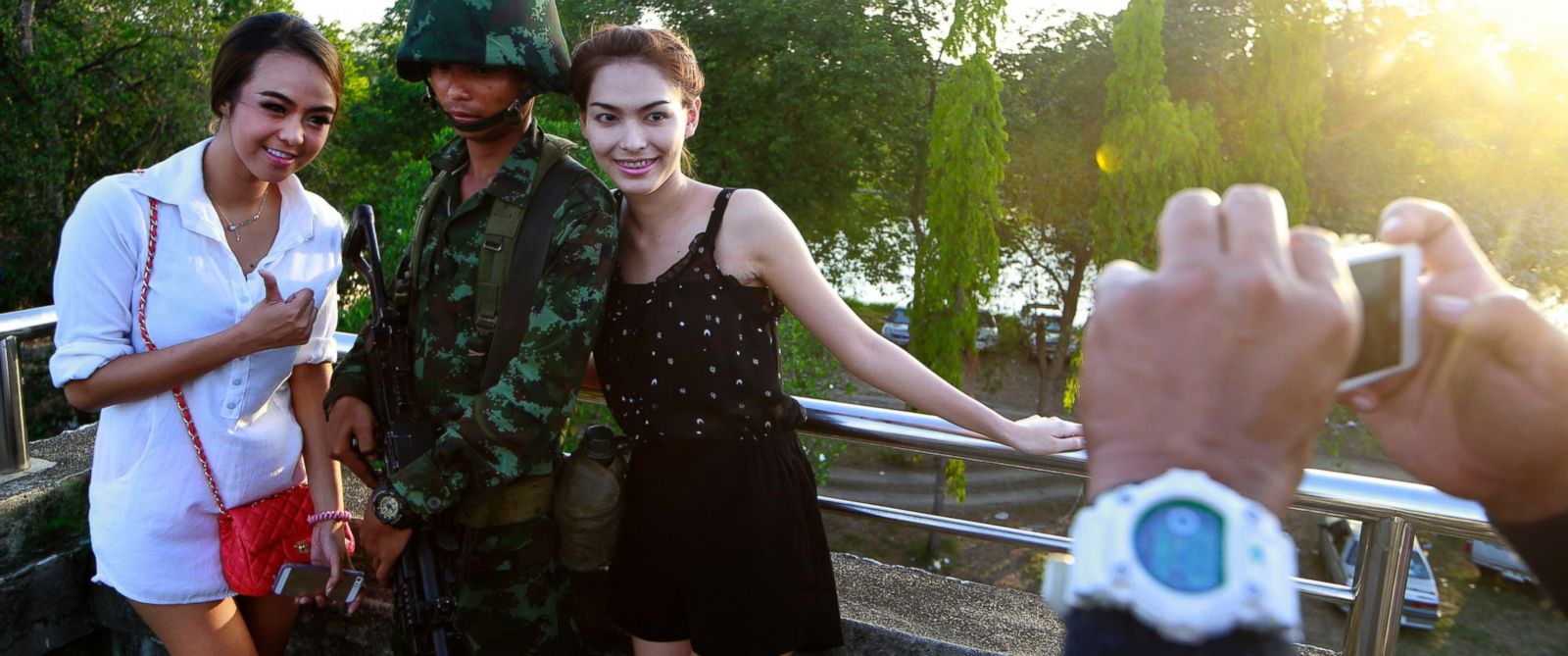 PHOTO: Passersby have their photograph taken with a Thai soldier guarding a pedestrian overfly near the site where pro-government demonstrators stage a rally on the outskirts of Bangkok, May 20, 2014.
