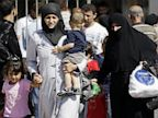 PHOTO: Syrian refugees pass through the Turkish Cilvegozu gate border, Saturday, Aug. 31, 2013.