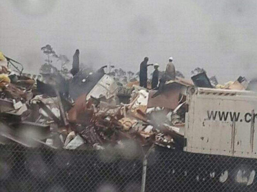People inspect the wreckage following a jet crash near Grand Bahama International Airport in Freeport, Bahamas, Nov. 9, 2014.