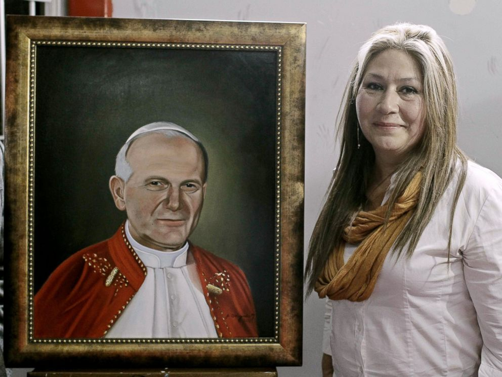 PHOTO: Costa Rican citizen Floribeth Mora, who was healed from a brain aneurysm through a miracle that is attributed to Pope John Paul II, poses next to a portrait of him during a press conference in San Jose, Costa Rica, April 22, 2014.