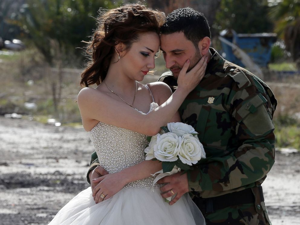 Newly-wed Syrian couple Nada Merhi, and Syrian army soldier Hassan Youssef, pose for a wedding picture amid heavily damaged buildings in the war ravaged city of Homs on Feb. 5, 2016.