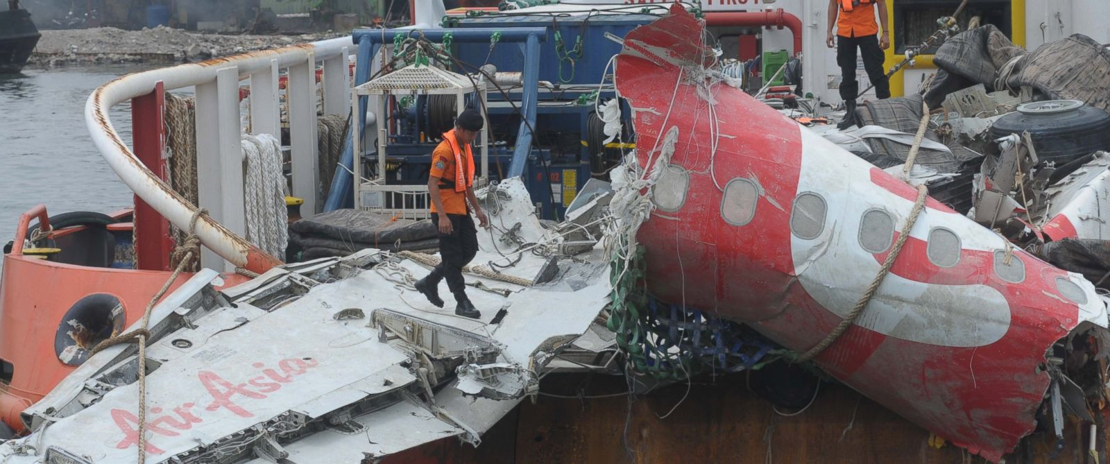 PHOTO:Indonesian rescuers stand next to the remains of crashed AirAsia flight QZ8501 on board of the Crest Onyx ship, after it was hoisted from the Java Sea during their recovery mission, March 2, 2015 in Jakarta, Indonesia.