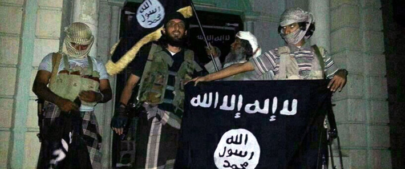 PHOTO: A picture taken with a mobile phone early on May 24, 2014 shows Al-Qaeda militants posing with Al-Qaeda flags in front of a museum in Seiyun, second Yemeni city of Hadramawt province.