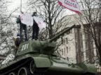 PHOTO: Pro-Russian demonstrators hold placards reading Crimea for peace as they stand on a T-34 Soviet tank, set as a WWII monument in front of the Crimean parliament in Simferopol, Feb. 27, 2014.