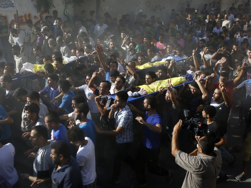 PHOTO: Palestinian mourners shout slogans during the funeral of four boys killed in an attack on a beach in Gaza City, July 16, 2014.