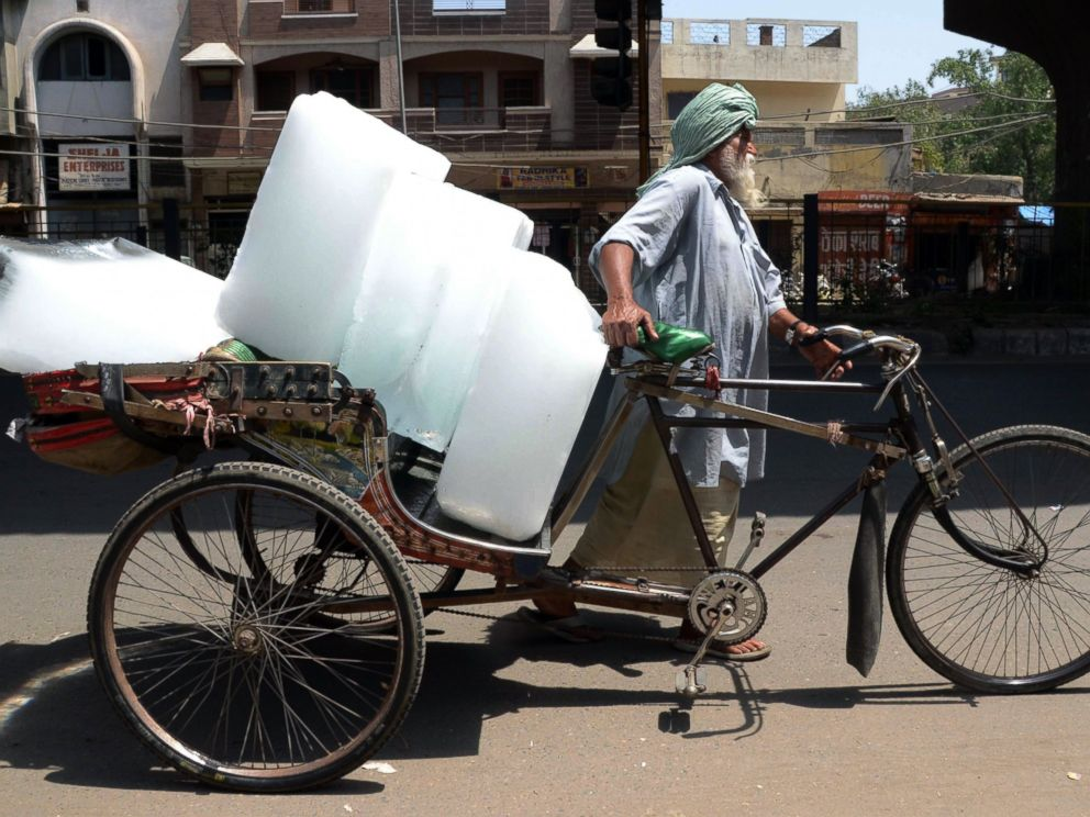 PHOTO: An Indian worker uses a ricksahw to transport ice from an ice factory in Amritsar on May 27, 2015.