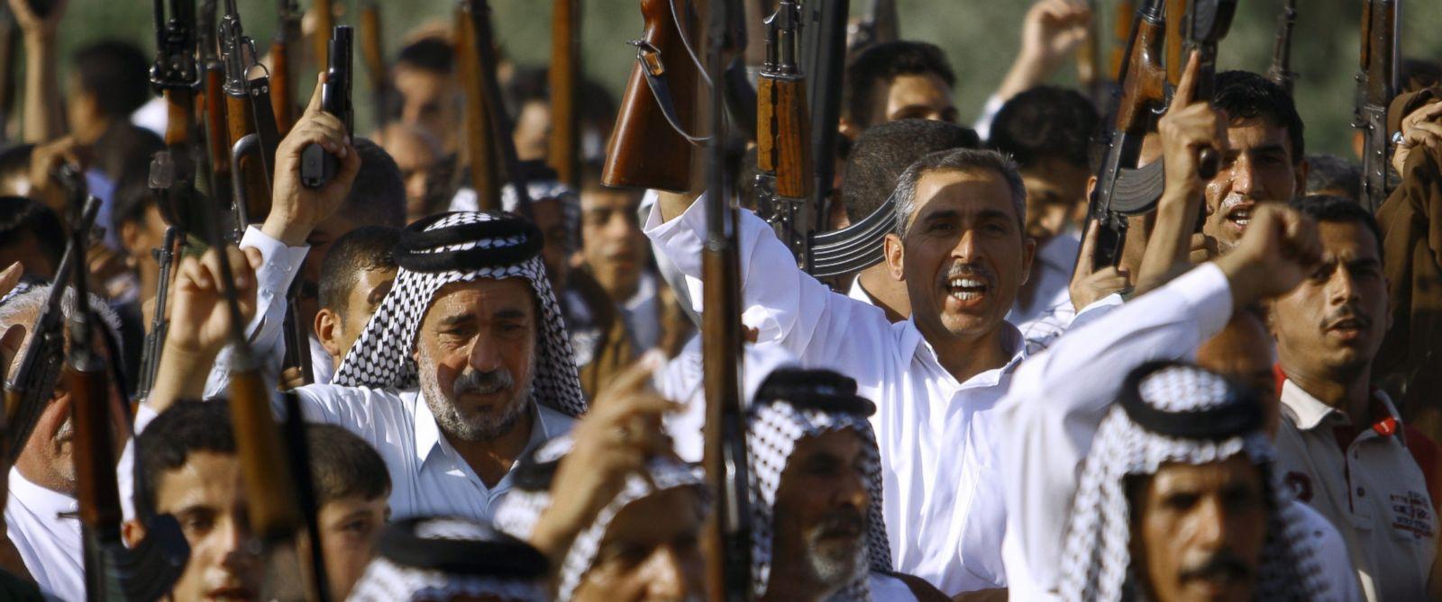PHOTO: Iraqi Shiite tribesmen brandish their weapons, June 16 2014, in the southern Shiite Muslim shrine city of Najaf.