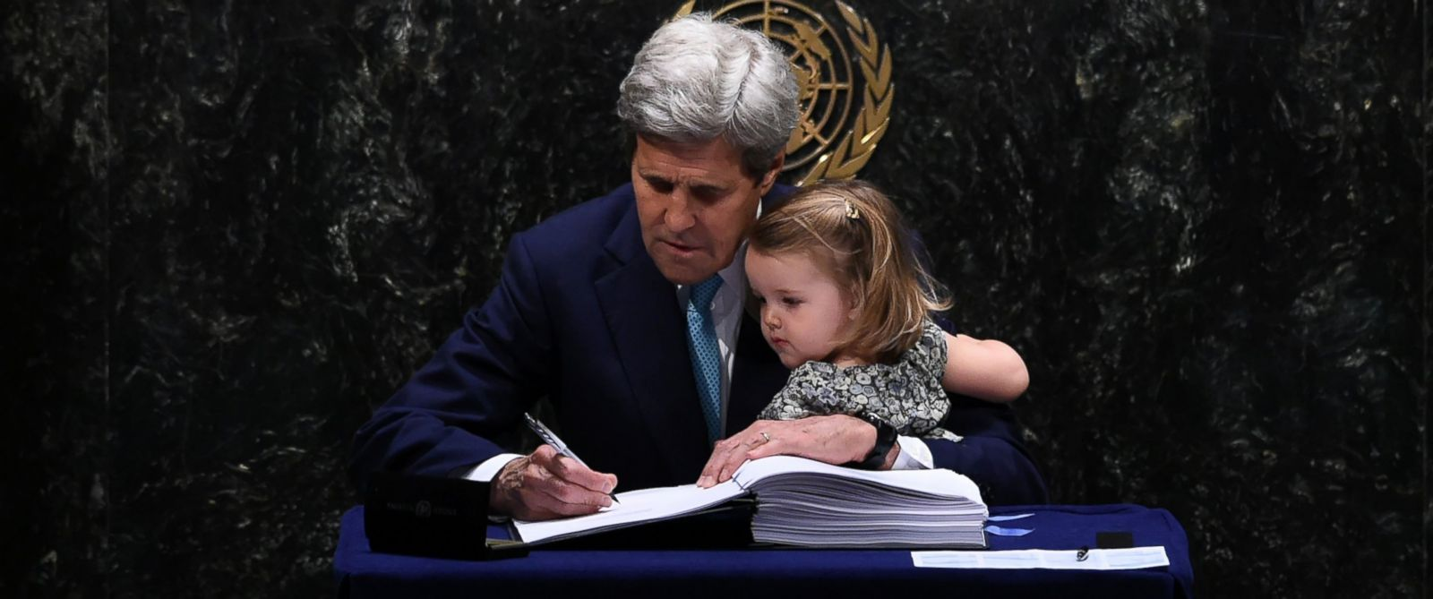 PHOTO: Secretary of State John Kerry signs the Paris Agreement at the United Nations General Assembly Hall while holding his granddaughter, Isabelle Dobbs-Higginson, April 22, 2016, in New York.