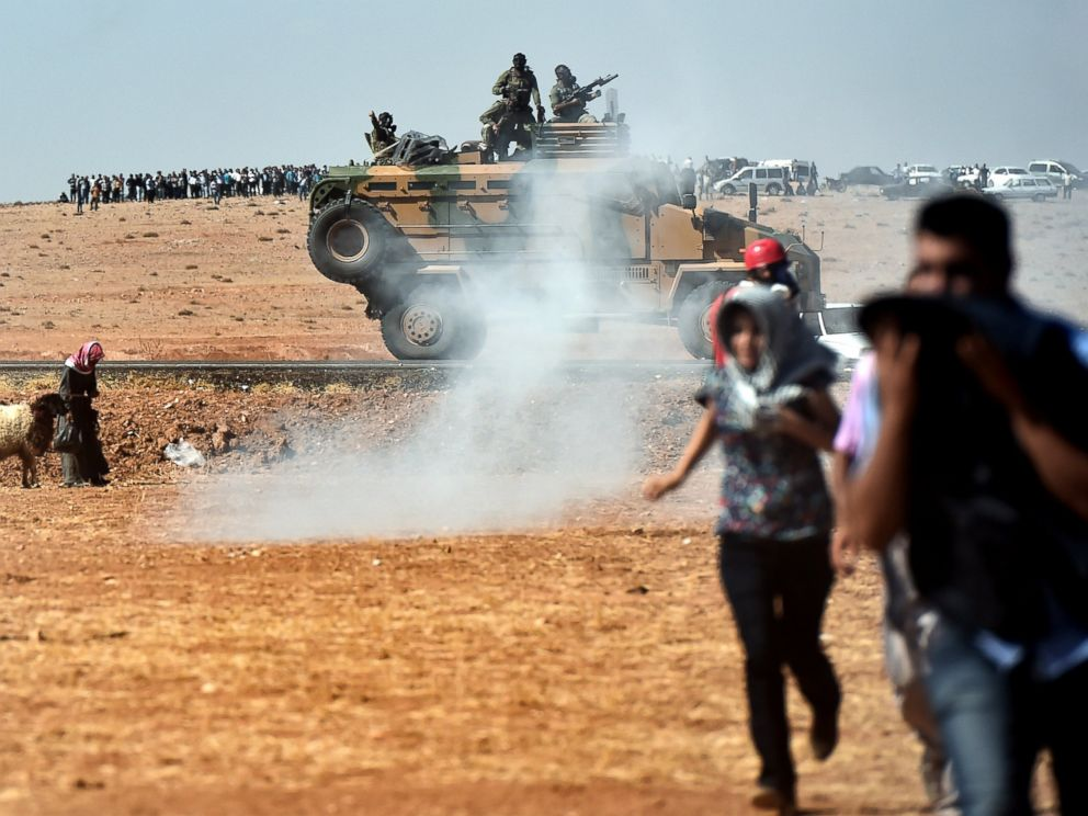 PHOTO: Kurdish people run away from tear gas as Turkish army tries to remove them from the Turkish-Syrian border area near the Syrian town known as Kobani by the Kurds, in the southeastern town of Suruc, Turkey, Oct. 7, 2014.