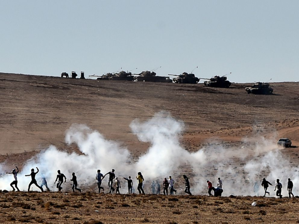 PHOTO: Kurdish people throw stones at Turkish armored vehicles near the Syrian town known as Kobane by the Kurds, in the southeastern town of Suruc, Sanliurfa province, Turkey, Oct. 7, 2014.