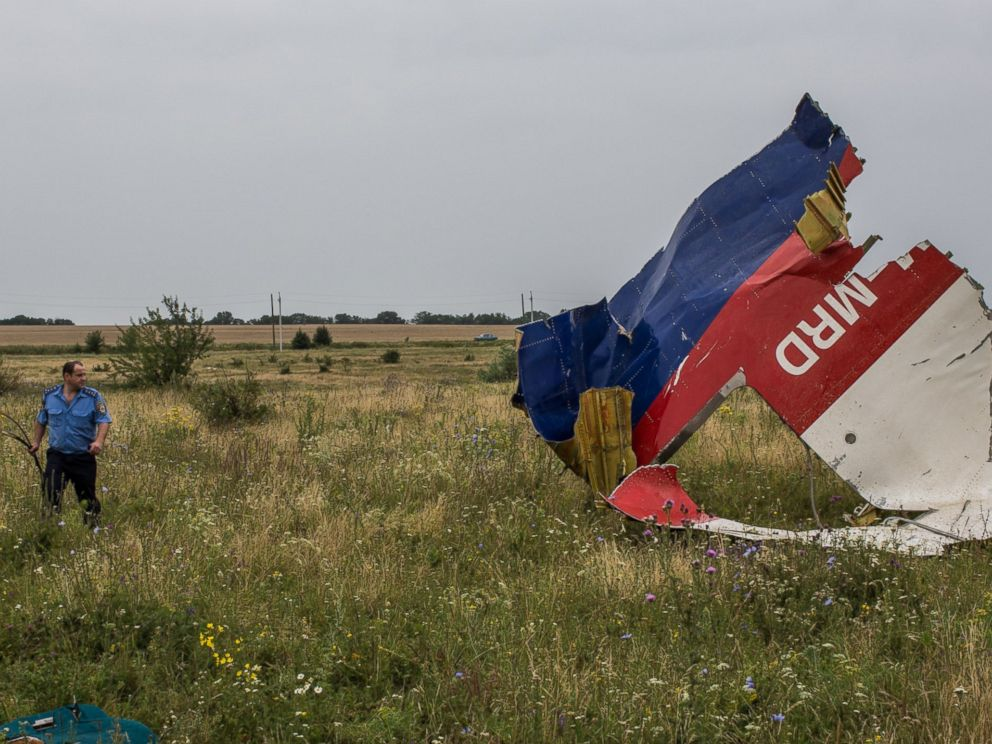 PHOTO: A Ukrainian police officer searches for human remains from Malaysia Airlines Flight 17 on July 18, 2014 in Grabovka, Ukraine.