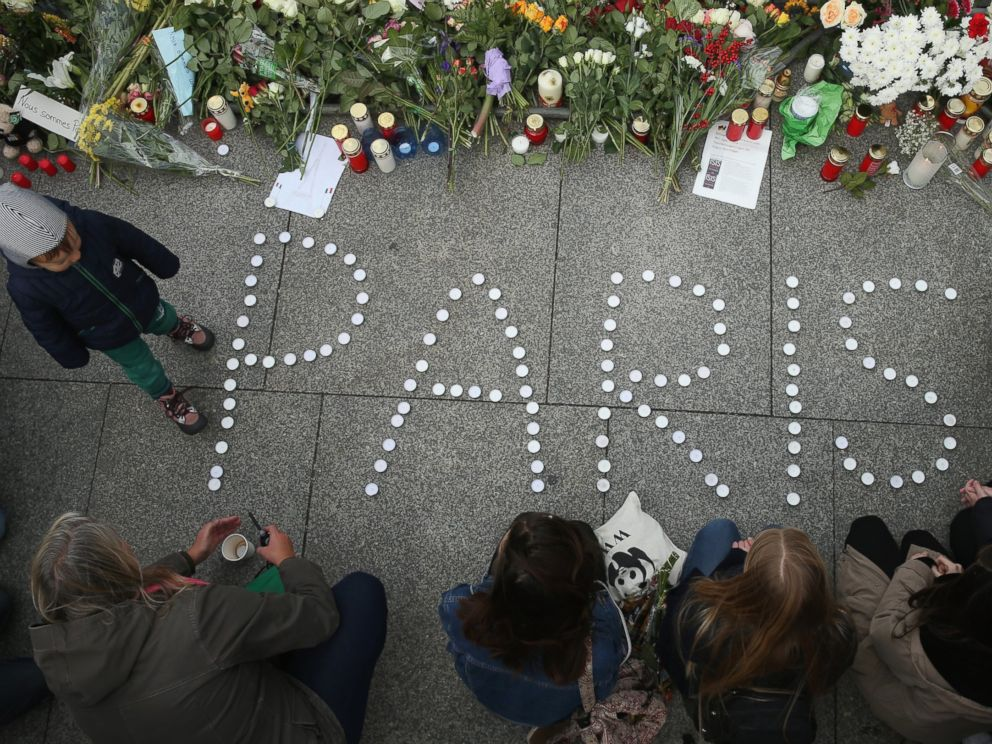 PHOTO: People finish arranging candles into the word Paris next to flowers and messages left at the gate of the French Embassy following the recent terror attacks in Paris, Nov. 14, 2015 in Berlin.