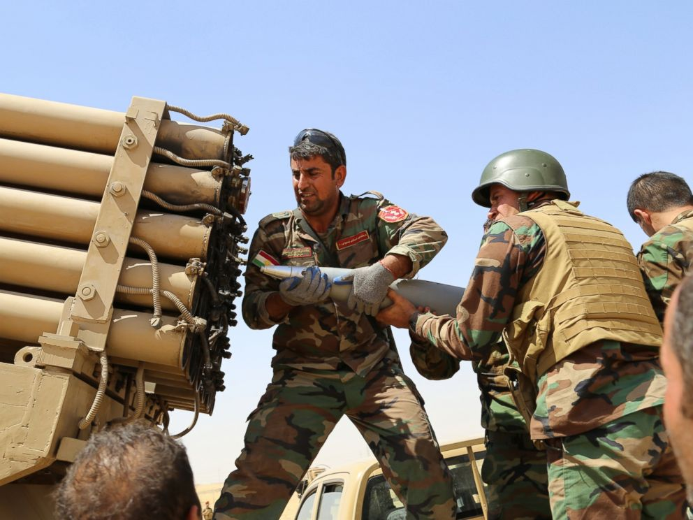 PHOTO: Kurdish peshmerga fighters load a missile launcher