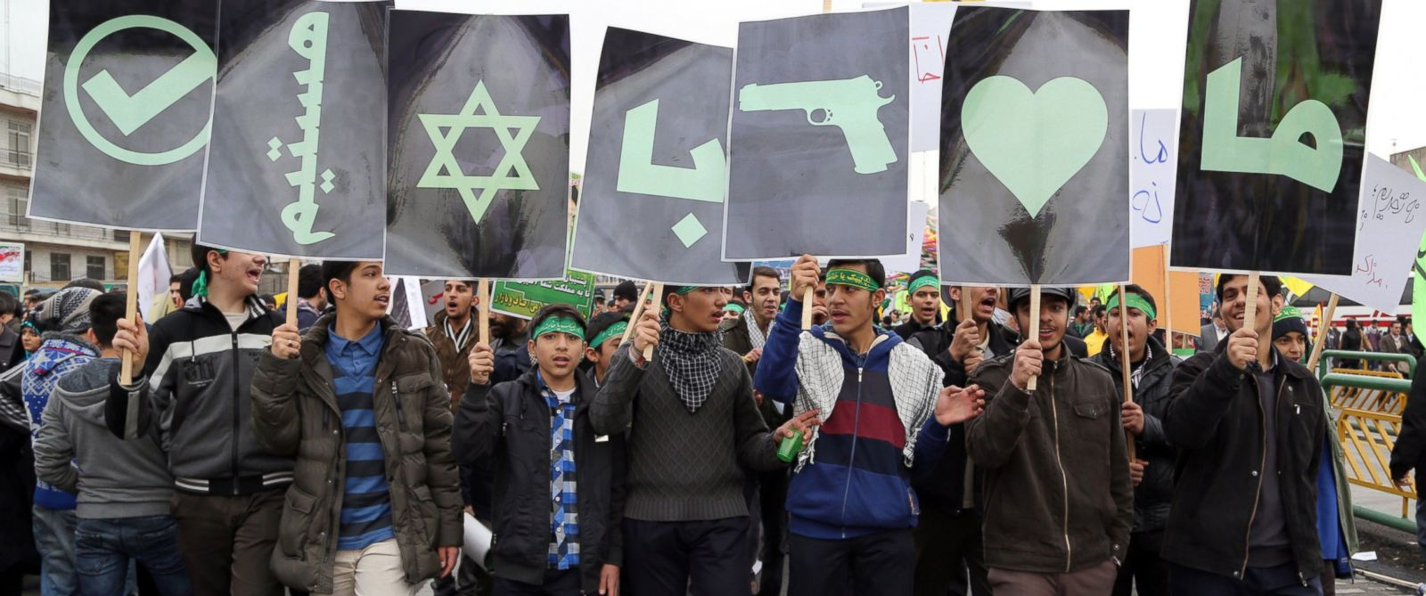 PHOTO: Iranians hold posters bearing signs and Persian text in favor of fighting Israel during a rally in Tehrans Azadi Square (Freedom Square) to mark the 36th anniversary of the Islamic revolution, Feb. 11, 2015.