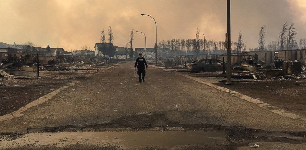 PHOTO: A Mountie surveys the damage on a street in Fort McMurray, Alberta, Canada May, 6th, 2016.