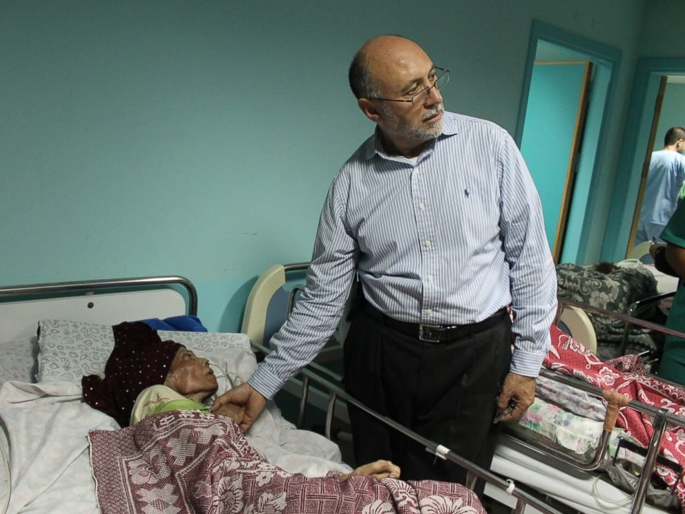 PHOTO: Basman Alashi, executive director of el-Wafa Hospital in eastern Gaza City, comforts a patient hours after an Israeli projectile struck the hospitals fourth floor Friday evening, demolishing a wall and damaging doors and windows.