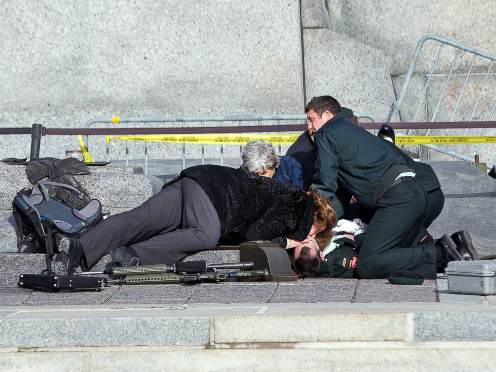 PHOTO: Police, bystanders and soldiers aid a fallen soldier at the War Memorial as police respond, Oct. 22, 2014 in Ottawa.