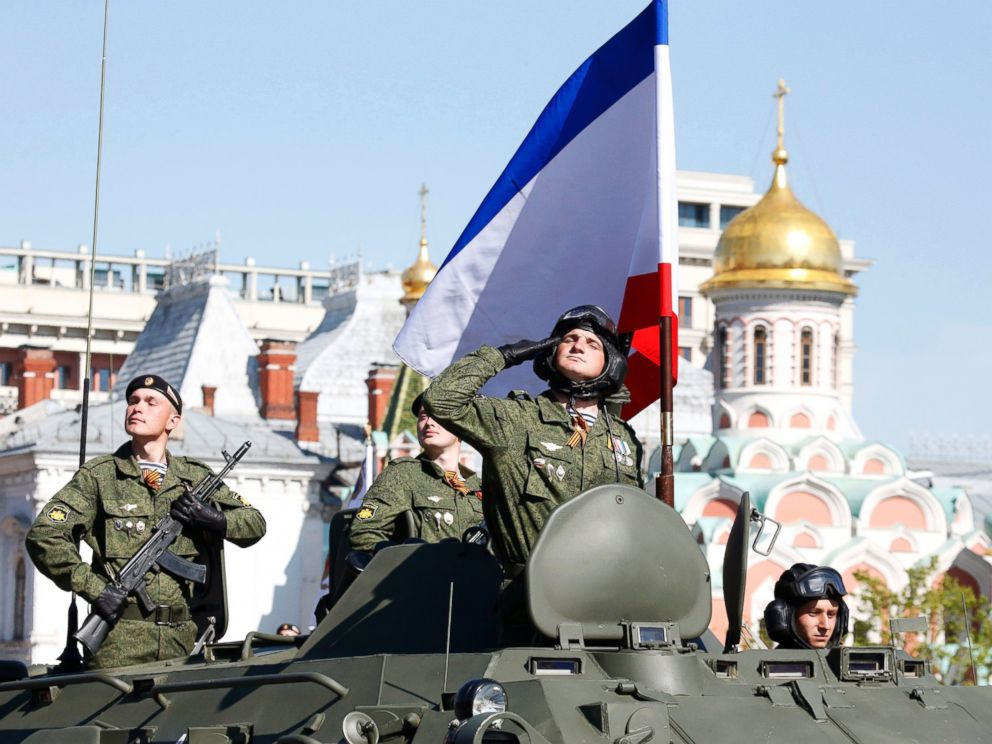 PHOTO: A Russian serviceman aboard an armored personnel carrier salutes next to the blue-white-red tricolor flag of Crimea, during the Victory Day parade at Red Square in Moscow, Russia on May 9, 2014.