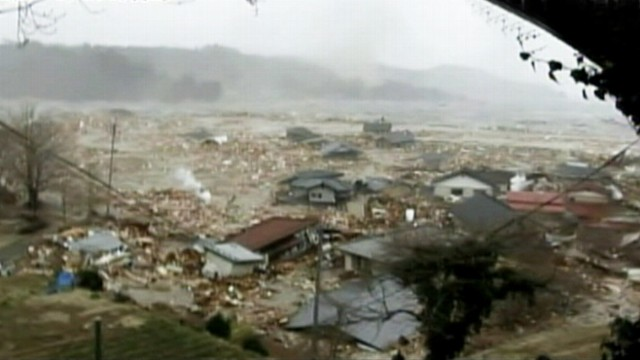 VIDEO: Onlookers scream as tsunami rips through town of Minamisanriku.