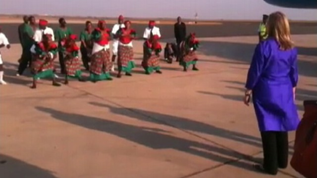 VIDEO: Secretary of State watches dancers on the tarmac before boarding her plane.