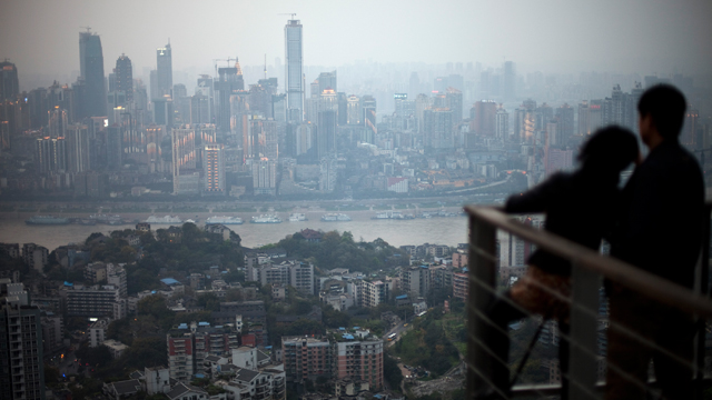 PHOTO: In this, April 3, 2012 photo, a couple observe the city skyline at a viewpoint in southwestern China's Chongqing city.