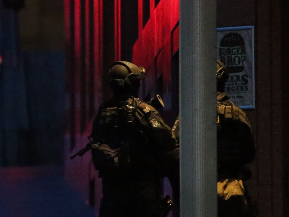 PHOTO: Armed tactical response police personnel stand watch into the evening near a cafe under siege by a gunman at Martin Place in the central business district of Sydney, Australia, Dec. 15, 2014.