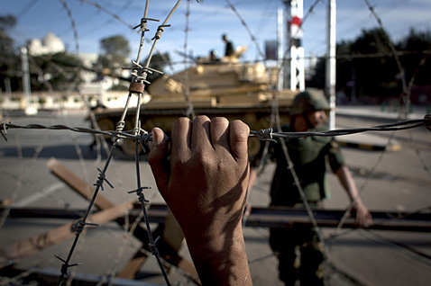 ap egypt barbed wire nt 121206 wblog Today in Pictures: Egypt Protests, Mother and Son, Santeria Devotees