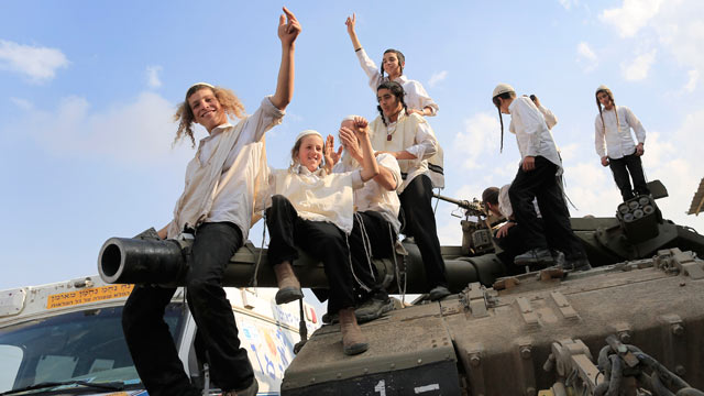 PHOTO: Ultra-Orthodox Jews of the Bratslav Hasidic sect, that gathered to show support for the forces, dance as they celebrate atop of a tank in southern Israel, close to the Israel Gaza Strip Border, Nov. 22, 2012.