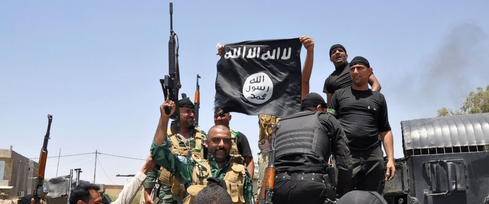 PHOTO: Iraqi security forces hold up a flag of the the jihadist group ISIS that they captured during an operation to regain control of Dallah Abbas 35 miles outside of Baghdad, Iraq on Jun 28, 2014.