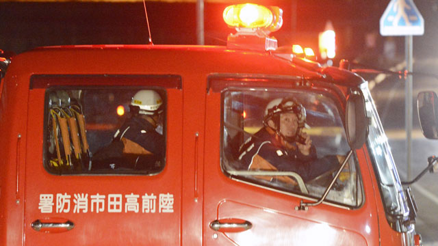 PHOTO:Firefighters in a fire fighting vehicle call for residents to evacuate from coastal areas in Rikuzentakata in Iwate Prefecture, Friday, Dec. 7, 2012, after a tsunami warning.