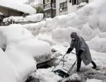 PHOTO: A man removes snow around a snow-covered vehicle in Yuzawa, Niigata prefecture, north of Tokyo, Feb. 1, 2012.