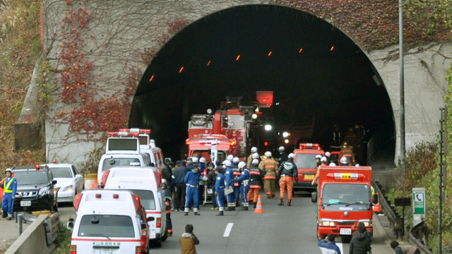 PHOTO: Police officers and firefighters gather at the exit of the Sasago Tunnel on the Chuo Expressway in Otsuki, Yamanashi Prefecture, central Japan, Sunday morning, Dec. 2, 2012.
