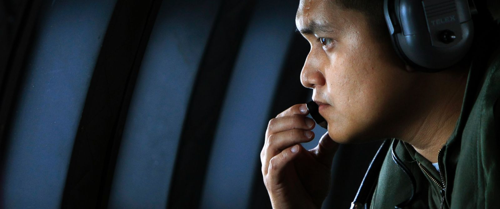PHOTO: A crew member of a Royal Malaysian Air Force CN-235 aircraft looks out the window during a search and rescue operation for the missing Malaysia Airlines plane over the Straits of Malacca, March 13, 2014.