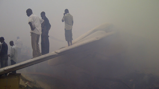 PHOTO: Onlookers stand on the tail wing of a crashed passenger plane in a neighborhood just north of Murtala Muhammed International Airport, in Lagos, Nigeria, Sunday, June 3, 2012.