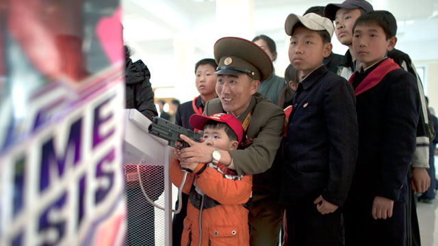 "PHOTO: A North Korean military officer plays a game called ""Time Crisis"" with his son at an amusement park in Pyongyang, North Korea, April 16, 2013."