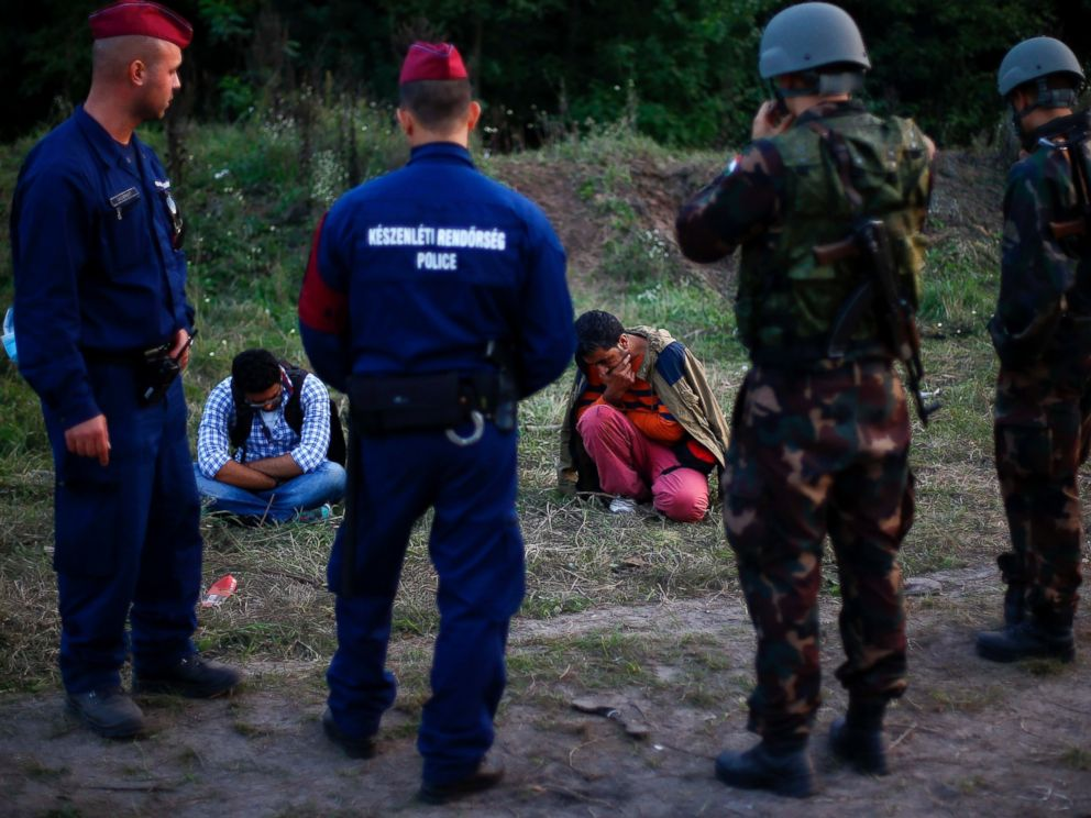 PHOTO: Migrants sit on the ground after they were arrested by Hungarian authorities after they tried to cross the border between Serbia and Hungary in Roszke, Hungary, Sept. 15, 2015.