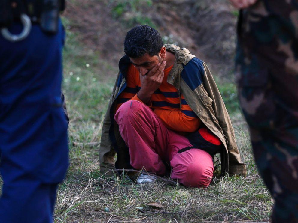 PHOTO: A migrant sits on the ground arrested by Hungarian authorities after he tried to cross the border between Serbia and Hungary in Roszke, Hungary, Sept. 15, 2015.