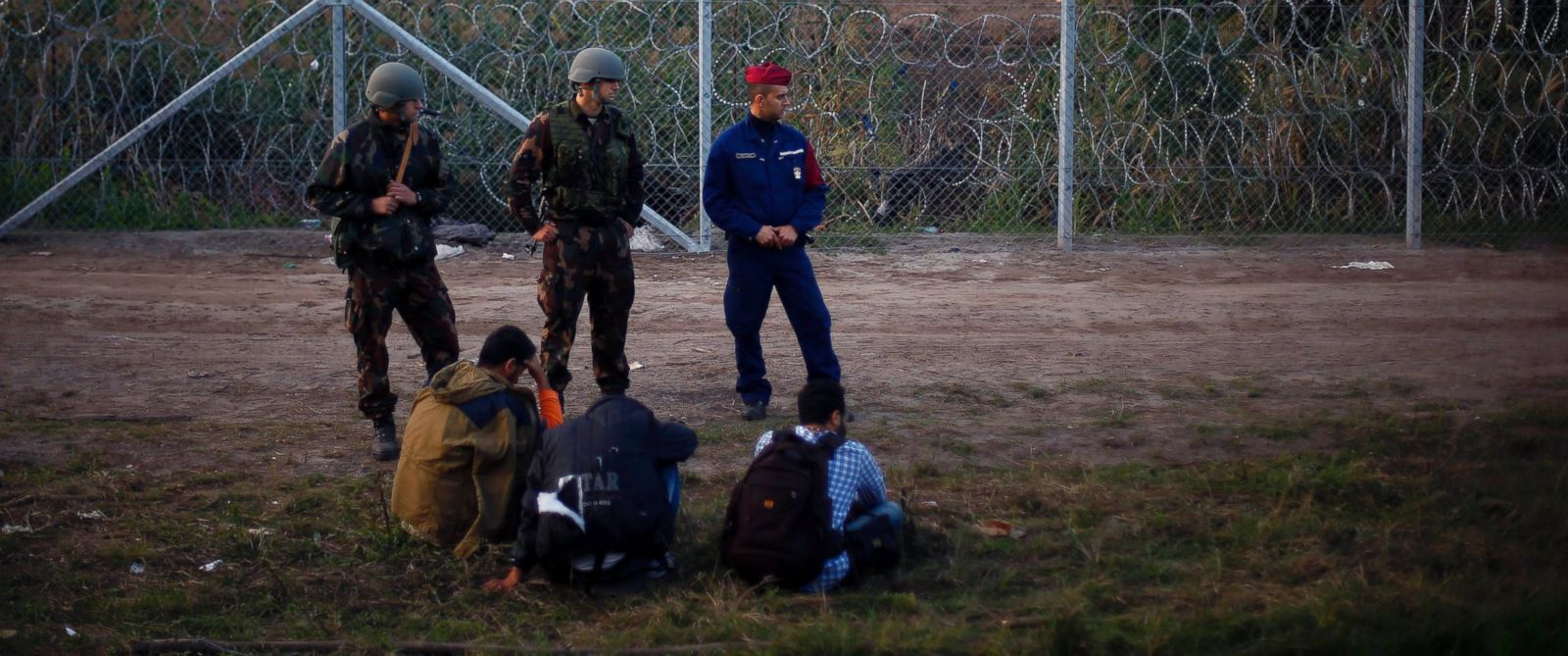 PHOTO: Migrants sit on the ground arrested by Hungarian police officers and soldiers after they tried to cross the border between Serbia and Hungary in Roszke, Hungary, Sept. 15, 2015.