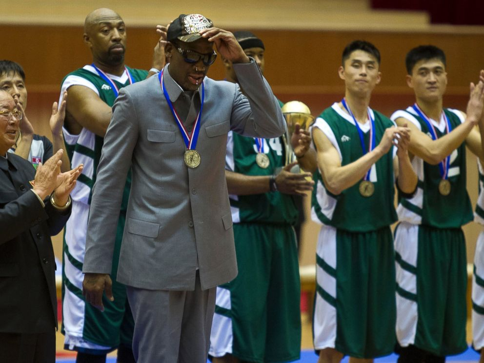 PHOTO: Dennis Rodman tips his hat as U.S. and North Korean basketball players applaud at the end of an exhibition basketball game at an indoor stadium in Pyongyang, North Korea on Jan. 8, 2014.