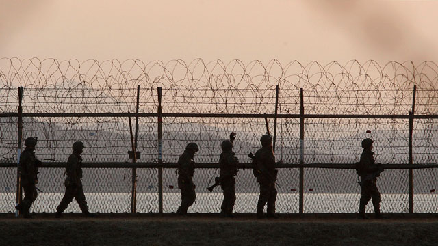 PHOTO: South Korean army soldiers patrol along a barbed-wire fence near the border village of Panmunjom in Paju, South Korea on March 26, 2013 after a warning from North Koreas military that its artillery and rocket forces are at their highest-level comb