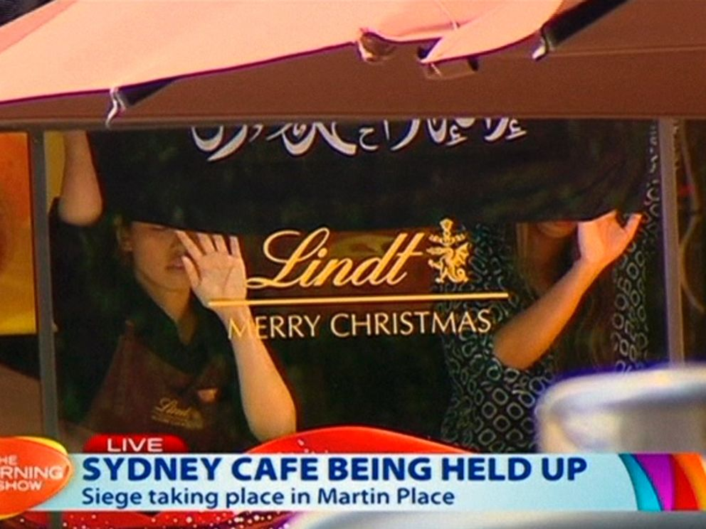 PHOTO: This image taken from video show people holding up what appeared to be a black flag with white Arabic writing on it, inside a cafe in Sydney, Australia, Dec. 15, 2014.