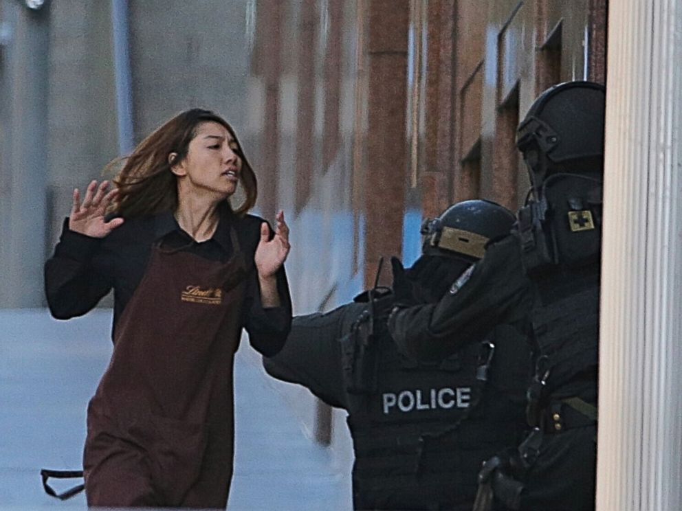 PHOTO: An armed tactical response police officer grabs a hostage as she flees from a cafe under siege at Martin Place in the central business district of Sydney, Australia, Dec. 15, 2014.