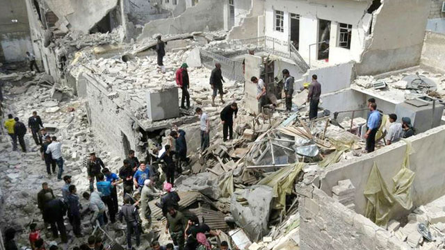 PHOTO: Syrian citizens stand on rubble of destroyed houses that were damaged by Syrian forces airstrike, in Aleppo, Syria, April 15, 2013.