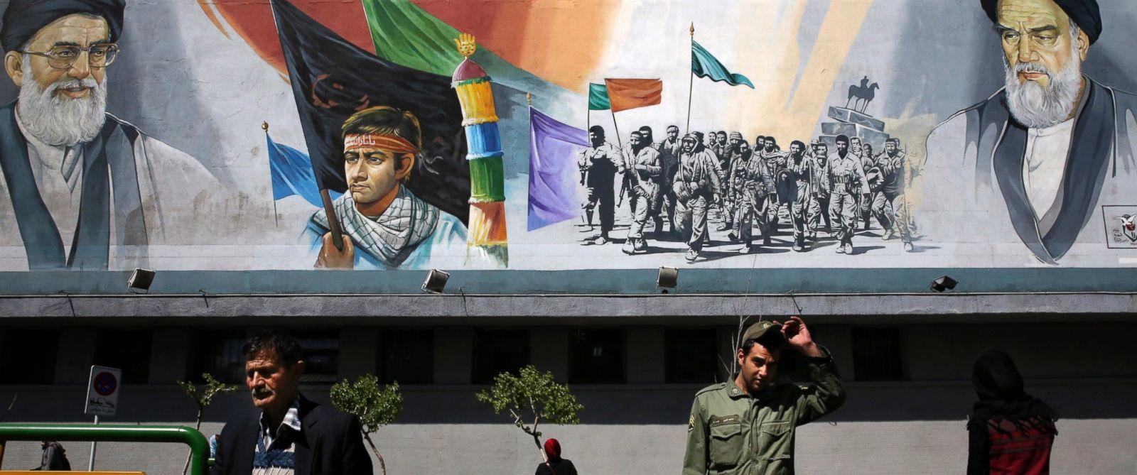 PHOTO: Pedestrians cross the Enqelab-e-Eslami street under a mural depicting the late Iranian revolutionary founder Ayatollah Khomeini, members of Basij paramilitary force and Supreme Leader Ayatollah Ali Khamenei in Tehran, Iran, March 31, 2015.