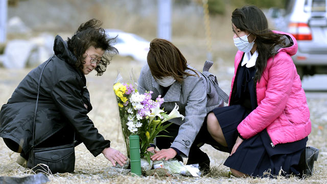 PHOTO: Yoko Yasuda, center, offers flowers where her parents house used to stand in Rikuzentakata, Iwate prefecture, northern Japan, March 10, 2013.