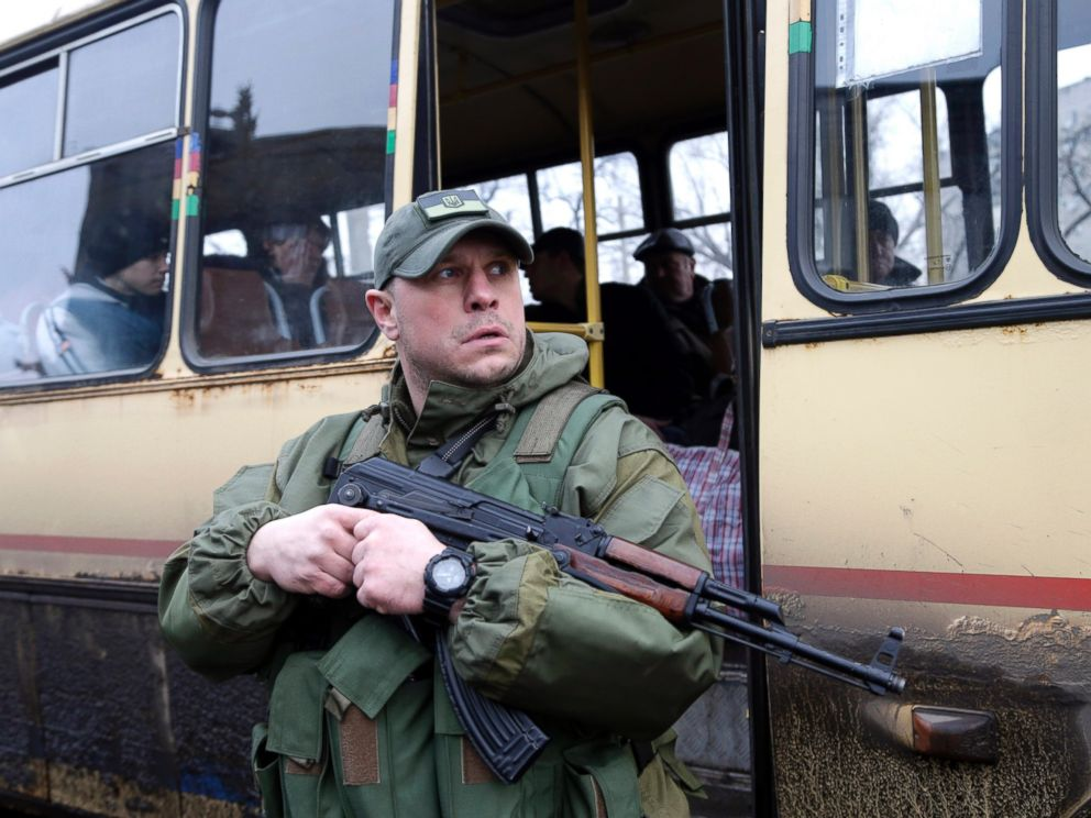 PHOTO: A Ukrainian soldier holds a weapon as people wait on a bus to leave the town of Debaltseve, Ukraine on Feb. 3, 2015.