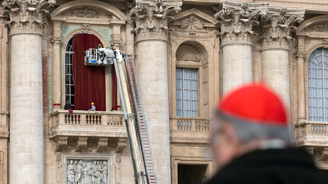 PHOTO: Workers use a crane to place a burgundy curtain around the door frame of the balcony on the front of St. Peters Basilica where the newly elected pope will make his first appearance at the Vatican, March 11, 2013.