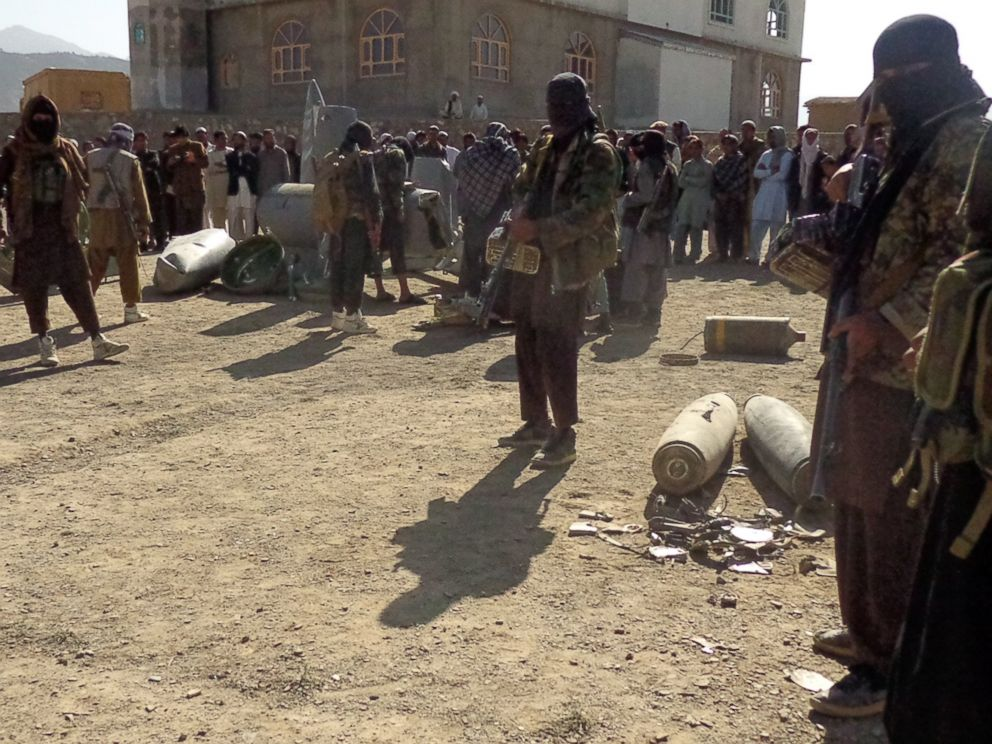 PHOTO: In this photograph taken on Oct.13, 2015, Afghan Taliban militants gather around parts of a US F-16 aircraft that was struck over in Sayid Karam district of eastern Paktia province.